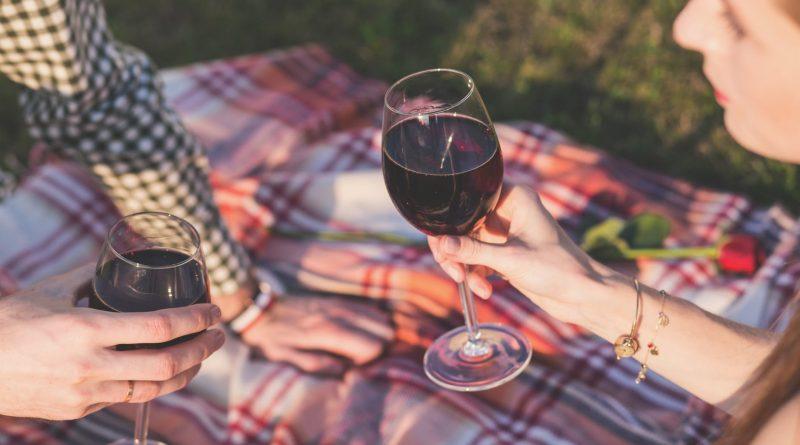 En kvinde og en made sidder udenfor på et tæppe og nyder et glas rødvin