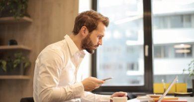 Mand i skjorte sidder foran sin computer med mobilen i hånden