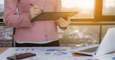 Kvinde står med en tablet og analyserer grafer