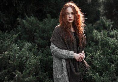 En rådhåret kvinde står med uldtøj på i en skov